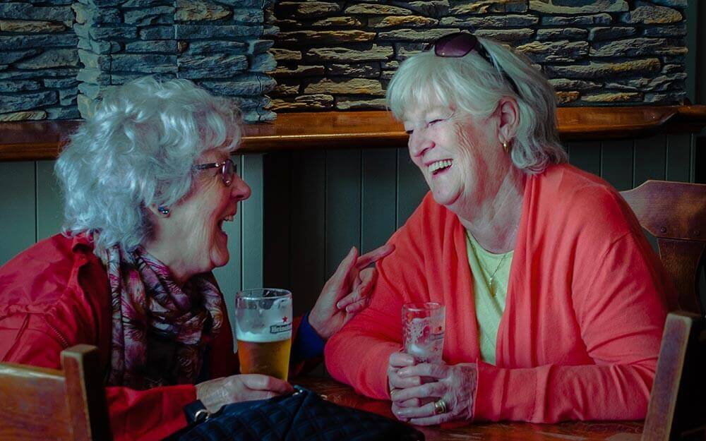 lions hoilday project photo of two ladies enjoying a drink and a joke at Trabolgan Holiday Village
