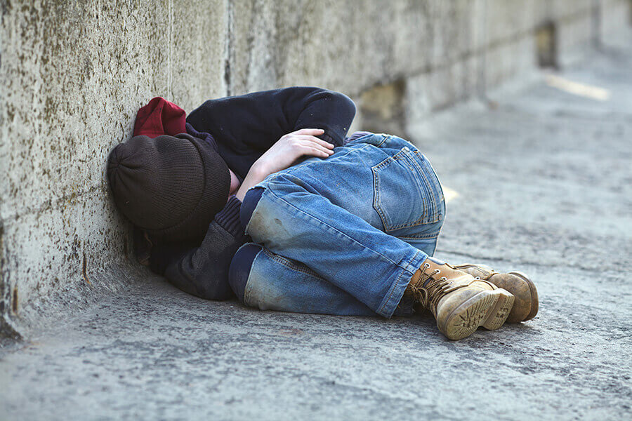 photo of a homeless child sleep on the streets